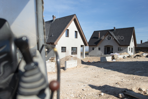 Excavator and new built houses - Stock Photo - Images
