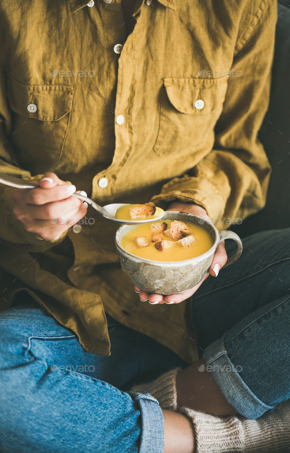 Woman sitting and eating pumpkin soup from mug - Stock Photo - Images