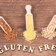 Free Download Gluten free inscription with buckwheat and millet groats on rustic board, healthy food concept Nulled