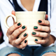 Free Download Stylish fashionable girl with a Cup of coffee and a green manicure in jeans. Fashion, care, beauty Nulled