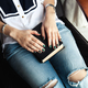Free Download Stylish girl in torn jeans reading a book with a beautiful green manicure Nulled