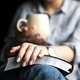 Free Download Young woman reading a book and holding cup of tea or coffee Nulled