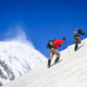 Two mountain trekkers on steep snowed hill with peaks background - PhotoDune Item for Sale
