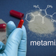 Free Download Hand with blue latex glove holds a capsule of metamizol, chemical composition, conceptual image Nulled