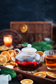 Glass teapot of hot black tea on cozy background with dried oran - PhotoDune Item for Sale