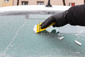 Hand holding scraper and removing ice or snow from car window - PhotoDune Item for Sale
