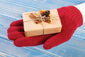 Hand in gloves with decorated gift for Christmas or other celebration - PhotoDune Item for Sale