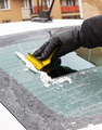Hand holding yellow scraper and removing ice or snow from car window - PhotoDune Item for Sale