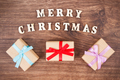 Inscription Merry Christmas with wrapped gifts on rustic board - PhotoDune Item for Sale