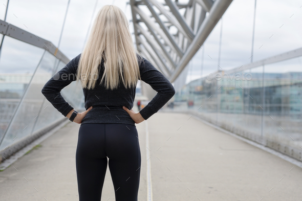 Fit blonde woman runner standing on bridge in modern looking city - Stock Photo - Images