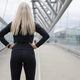 Fit blonde woman runner standing on bridge in modern looking city - PhotoDune Item for Sale
