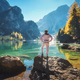 Free Download Man on the stone on the coast of Braies lake at sunrise Nulled