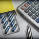 Blister pack of pills next to a calculator, concept of copayment health - PhotoDune Item for Sale