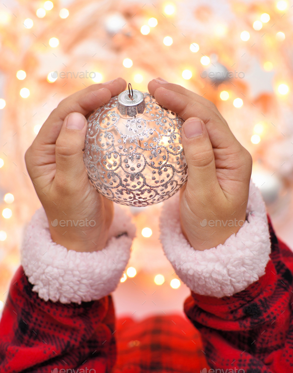 Christmas decoration ball in the children's hands against the ba - Stock Photo - Images