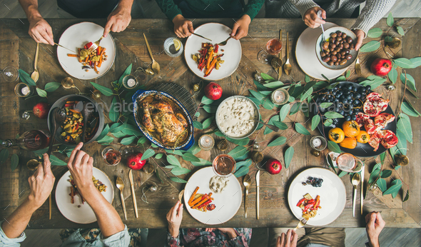 Friends or family eating at festive Christmas table, top view - Stock Photo - Images