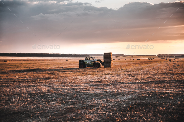 Loading of straw on the car in the field - Stock Photo - Images