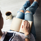 Young modern girl in torn jeans reading a book with a big cup of coffee. lifestyle, education - PhotoDune Item for Sale