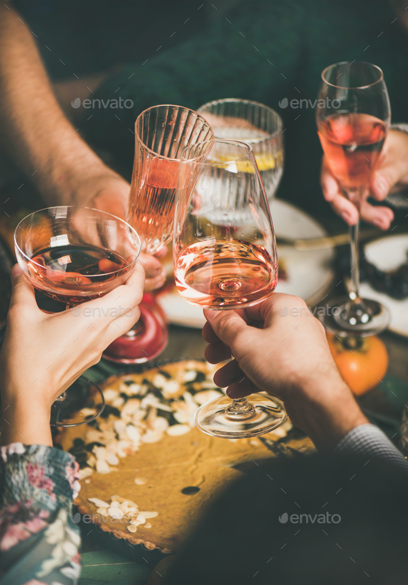 Friends clinking glasses with rose wine at Christmas festive table - Stock Photo - Images