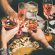 Friends clinking glasses with rose wine at Christmas festive table - PhotoDune Item for Sale