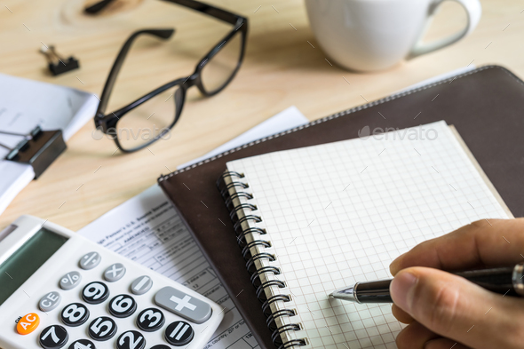 young man hand using calculator and writing - Stock Photo - Images