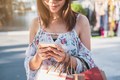 Young woman using smartphone with shopping bags at shopping mall - PhotoDune Item for Sale