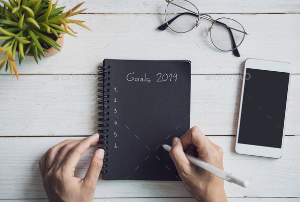 2019 goals text on notebook with smartphone on white wooden desk - Stock Photo - Images