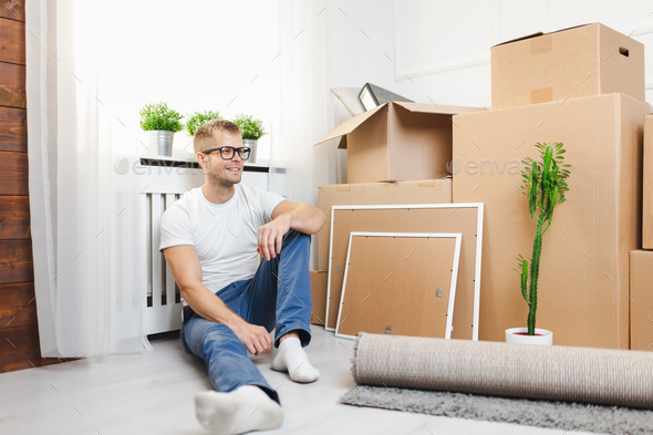 Handsome young man moving to a new home - Stock Photo - Images