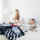 Travelling with kids. Happy mother with her child packing clothes for holiday - PhotoDune Item for Sale