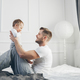 Happy father with his son playing at home on the bed - PhotoDune Item for Sale