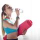 Beautiful caucasian woman drinking water while holding yoga mat - PhotoDune Item for Sale