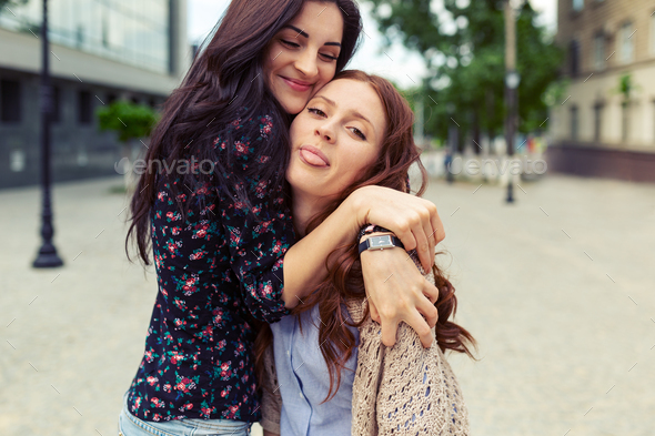 Carefree smiling sisters hugging and having fun together - Stock Photo - Images