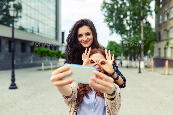 Two girls making funny selfie on the street, having fun together - Stock Photo - Images