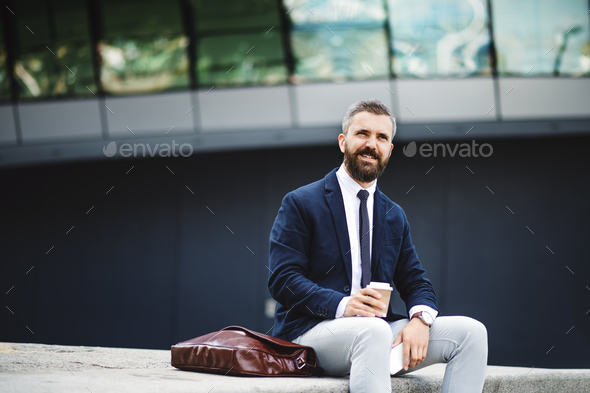 Hipster businessman with coffee and smartphone sitting outdoors in the city. - Stock Photo - Images