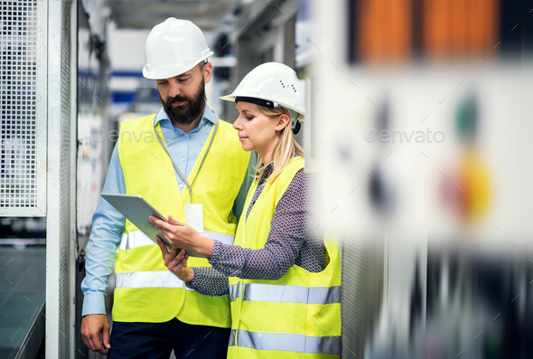 A portrait of an industrial man and woman engineer with tablet in a factory, talking. - Stock Photo - Images