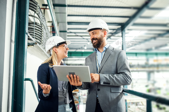 A portrait of an industrial man and woman engineer with tablet in a factory, working. - Stock Photo - Images