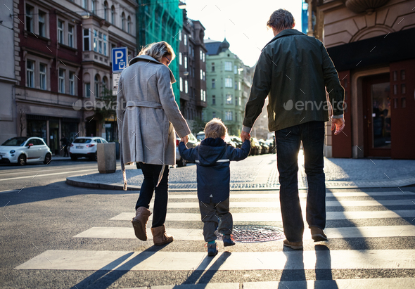 A rear view of small toddler boy with parents crossing a road outdoors in city. - Stock Photo - Images