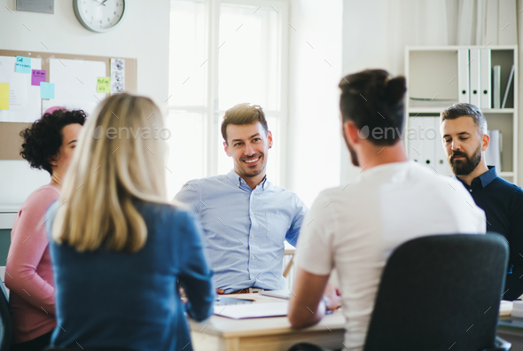 Group of young businesspeople sitting around table in a modern office, having meeting. - Stock Photo - Images