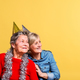 Free Download Portrait of a senior women in studio on a yellow background. Party concept. Nulled