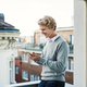 Free Download Young man with smartphone standing on a balcony in city, text messaging. Nulled
