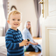 Free Download A toddler boy with young mother in the background inside in a bedroom. Nulled