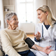 Free Download A health visitor measuring a blood pressure of a senior woman at home. Nulled