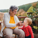 Elderly woman sitting with a toddler great-grandchild on a terrace in autumn. - PhotoDune Item for Sale