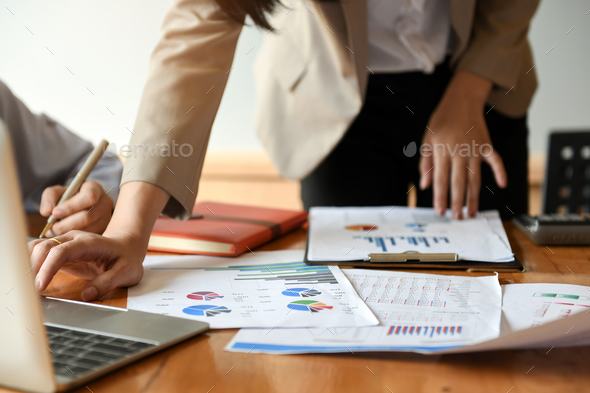 Female office are analyzing graphs data.They use a laptop. - Stock Photo - Images