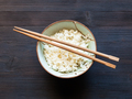 chopsticks above boiled rice in cup on dark table - PhotoDune Item for Sale