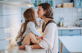 Mom kisses her little daughter in the kitchen - PhotoDune Item for Sale
