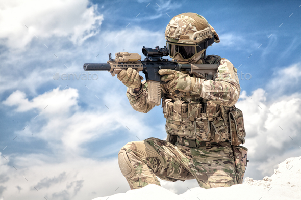 Airsoft game participant aiming with rifle replica - Stock Photo - Images