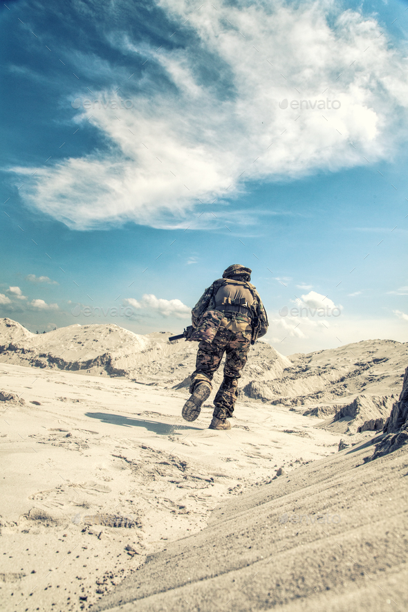 Man in military uniform playing airsoft in sands - Stock Photo - Images