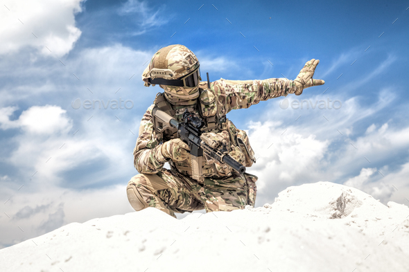Equipped airsoft player showing halt hand signal - Stock Photo - Images