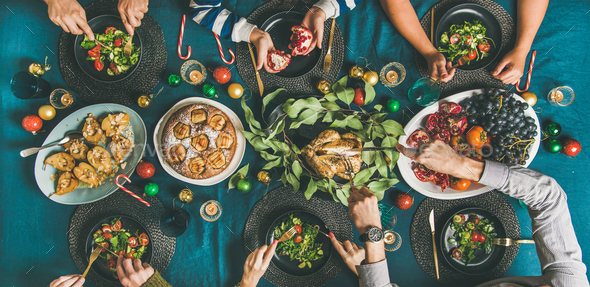 Human hands eating different meals at Christmas party dinner - Stock Photo - Images