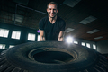 Shirtless man flipping heavy tire at gym - PhotoDune Item for Sale